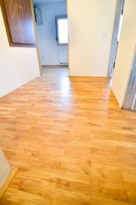 Renovating old apartment and parquet wooden hard floor. Empty room with white walls. Shiny new floor.